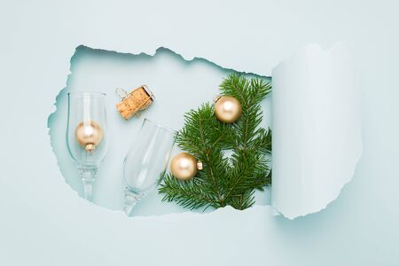 New Year layout and a big hole on paper background mint color. Christmas toys glasses goblets a blue bright background.