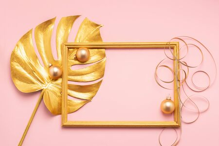 Leaf of a tropical plant frame Christmas balls serpentine painted gold pink background. Art concept. Festive minimalism.