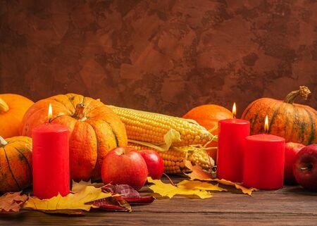 Autumn still life ripe pumpkin apples corn fallen yellow leaves candles dark background. Thanksgiving Autumn Concept.