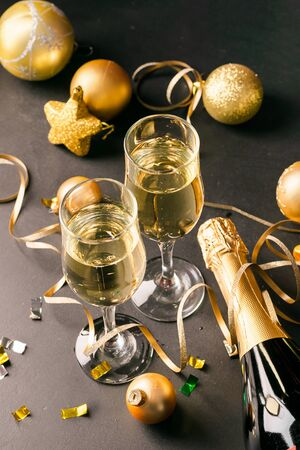 Champagne in glass goblets a bottle of New Years toys serpentine stars black background. New year christmas concept.