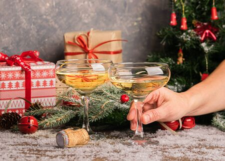 Woman holds a glass of champagne. Sparkling wine in elegant glass glasses on a festive Christmas table with gifts and a decorated Christmas tree. New Year concept. Selective focus. Horizontal frame