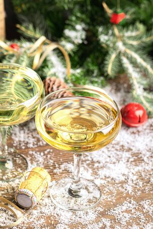 Two glasses of champagne sparkling wine close-up cork on a festive Christmas decorated table. New Year concept.