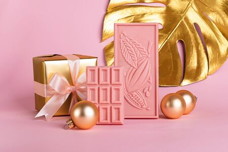 Chocolate pink tiles on a delicate pastel background and golden Christmas toys plant leaf. Front view. Festive minimalism concept. Copy space. Square frame