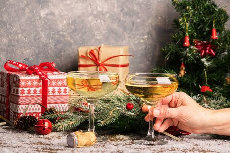 Woman fills a glass of champagne. Sparkling wine in elegant glasses on a Christmas table with gifts . New Year concept. Stockfoto
