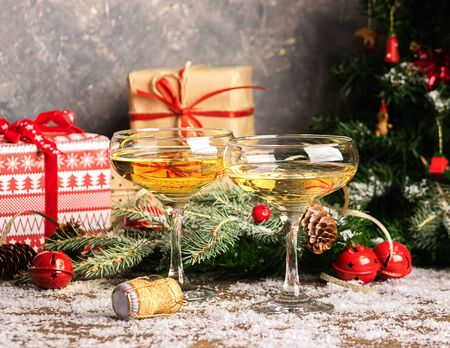 Champagne in two elegant glasses on a festive Christmas table with gifts a decorated Christmas tree. New Year concept.