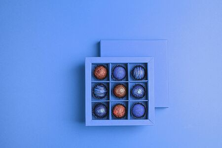Handmade chocolates in a blue box on a neon blue background. Flat top view. Copy space. Holiday Concept Minimalism