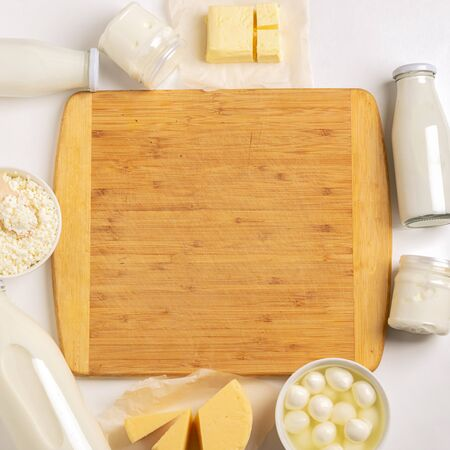 Dairy and sour-milk fermented organic products are laid out in a frame near cutting wooden board on a white background.