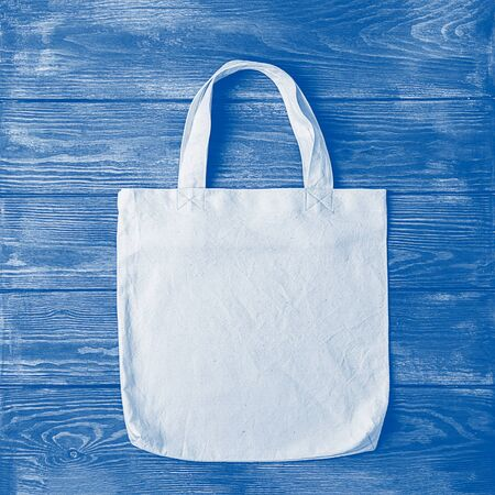 Bag with handles made of natural cotton for shopping products wooden background. Ecology concept. Minimalism.