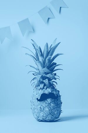 Funny tropical pineapple with a mustache on a blue background. Summer fashion concept with tinting effect. Copy space