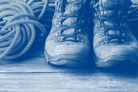 A pair of brown worn boots and a sport rope on a wooden background. Selective focus. Concept of travel and adventure.