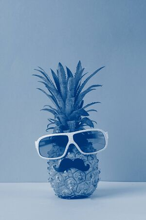 Funny dressed up pineapple in glasses with black mustache on a bright yellow blue background. Summer holiday concept.