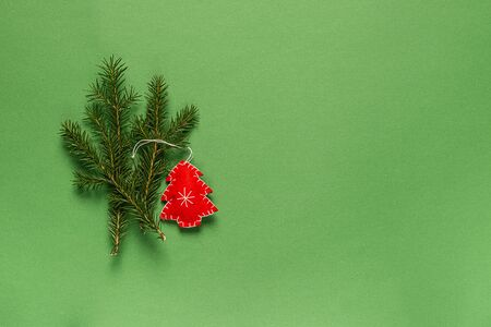 Christmas tree toy made from natural materials, fabric and fir branches on green background. Christmas holiday concept.