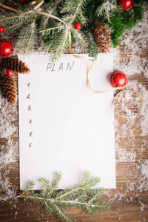 A sheet paper for planning pencil branches of spruce Christmas decorations wooden background. Festive concept New Year. Imagens