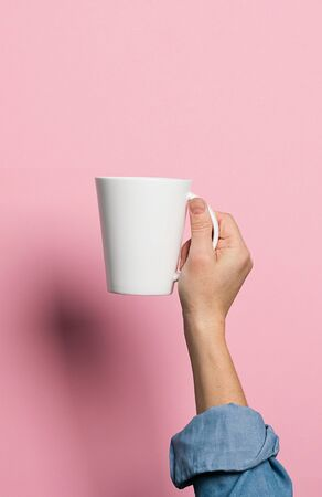 Woman holds in her hands a cup of coffee or tea drink pink background. Food drink concept. Copy space. Vertical frame