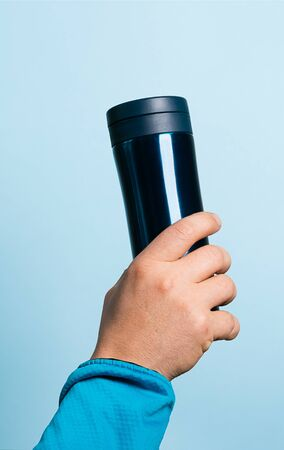 A man holds a flask mug high in his hand on blue background. Zero West Food Concept. Copy space for your text design.