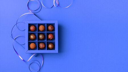 Chocolate candies festive box classic blue background. Holiday concept. Fashionable tinting minimalism. Flat top view.