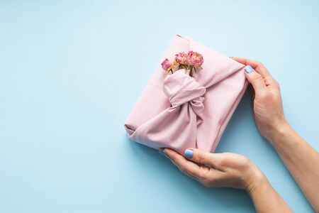 Female hands holding a holiday gift packed fabric in the manner of Furoshiki on a fashionable blue background.