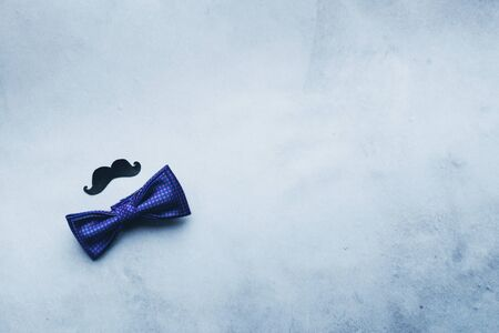 Decorative black mustache and blue bow-tie on a gray background. The concept of mens holiday fathers day. Top view