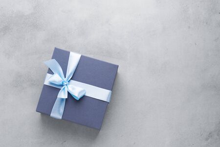 Gift blue box with satin ribbon on matching background. Horizontal frame copy space. Flat layout top view