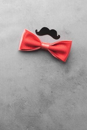 Decorative black mustache and red bow-tie on a gray background. The concept of mens holiday fathers day. Top view
