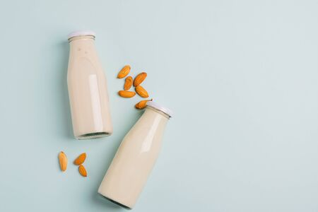 Almond nut milk drink in glass bottles light background. The concept of diet healthy eating. Horizontal frame copy space Imagens