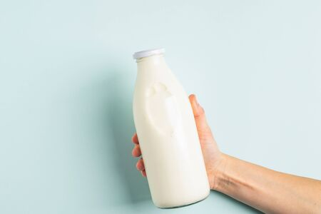 Female hand holds milk or white milk drink in a glass bottle on a white background. Healthy eating concept. Flat layout top view. Copy space. Horizontal frame