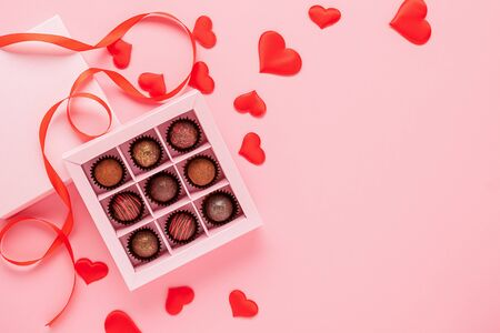 Handmade chocolates truffle in a box on a pink background with valentines. Valentines day concept festive food gifts. Imagens