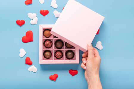 Female hand opens a box with chocolates blue background with hearts. Valentines day concept festive food gifts.