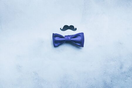 Mens tie butterfly black mustache photo props on a blue fashionable background. Concept of male holiday Flat layout