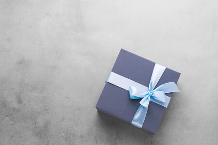 Festive box blue gift with satin bow on concrete gray background. Layout flat style. Holiday concept. Copy space