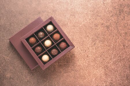 Handmade candies in a brown box on dark background. Flat top view. Copy space food holiday concept. Horizontal frame