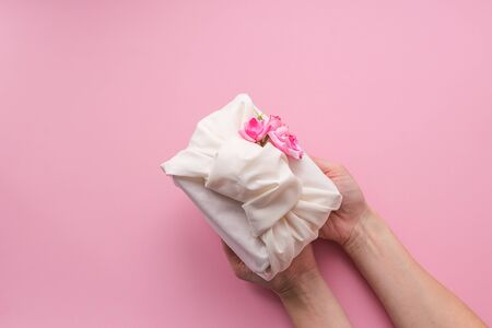 Female hands holding a holiday gift packed fabric in the manner of Furoshiki on a fashionable pink background.