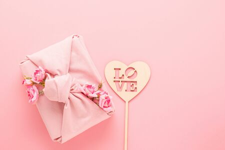 Holiday gift wrapped Furoshiki-style fabric and a heart made of natural material with the phrase love pink background.
