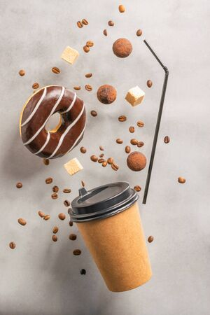 Disposable paper cup with a donut drink in chocolate icing candy truffles on a gray background. Creative levitation Imagens