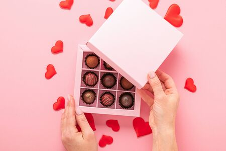 Female hand opens a box with sweets pink background with hearts. Gifts festive food love concept. Horizontal frame Imagens