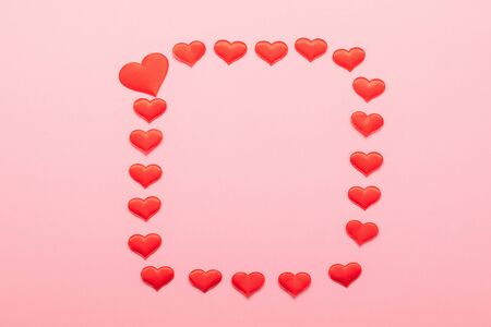 Red hearts symbol of love lined with a square frame on a pink background. Valentines day concept. Horizontal frame