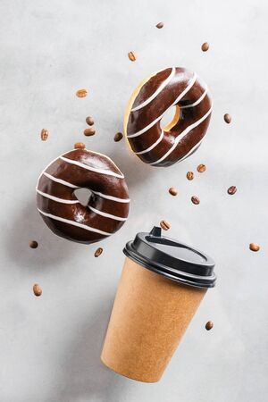 Paper cup with coffee drink or tea donut in chocolate coffee beans on a gray background. Creative fashionable levitation
