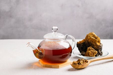 Healing tea from chaga birch mushrooms in a glass teapot. Organic drink antioxidant gray background.