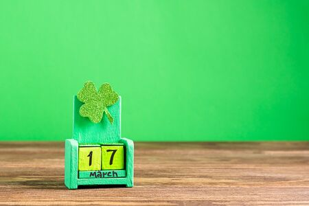 Block calendar with the date of March 17 and a trefoil leaf on green background. St. Patricks Day celebration concept. Imagens