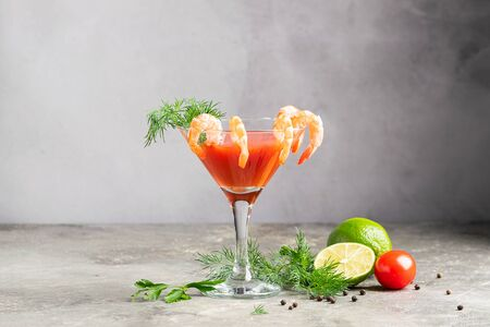 Cocktail tomatoes shrimp lemon juice sprig of dill and ingredients an elegant glass. Traditional drink gray background. 写真素材