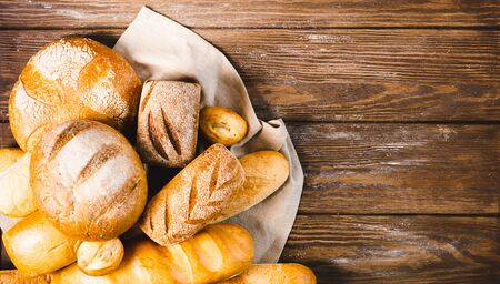Fresh baked bread with a golden crust, loaf, buns, white, rye on a rustic wooden background with sil rustic. Flat layout with place for advertisement.