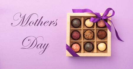 Set of different chocolates in a paper box with a satin ribbon on a bright background inscription Mothers Day.