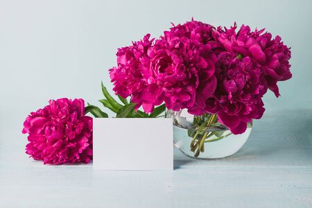 Beautiful burgundy pink peonies stand in a round vase on the table a greeting card. Template for text. Horizontal frame copy space