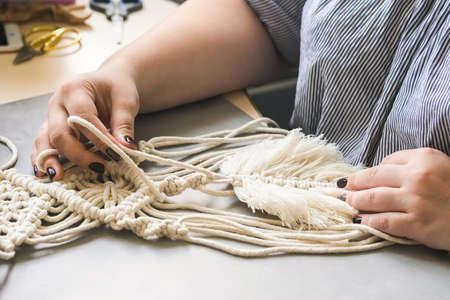 Female hands weave macrame the home workshop. Boho lifestyle. Hobby hobby concept. Selective focus horizontal frame. Standard-Bild