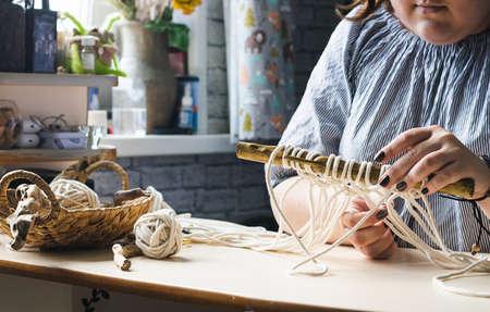 Female hands weave macrame the home workshop. Boho lifestyle. Hobby hobby concept. Selective focus horizontal frame.