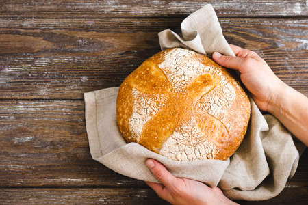 Hands holding a whole loaf of freshly baked bread with a golden crust. Homemade yeast-free pastries wooden background. Zdjęcie Seryjne