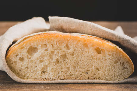 Fresh baked white bread slice slice on a dark background. Front view copy space.