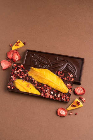 Chocolate dark Belgian bar with the addition of fruit slices of strawberry mango on a brown background. Dessert food