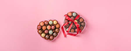 Chocolate candies truffle made of different colored chocolate in a heart shape box on a pink background. Dessert holiday