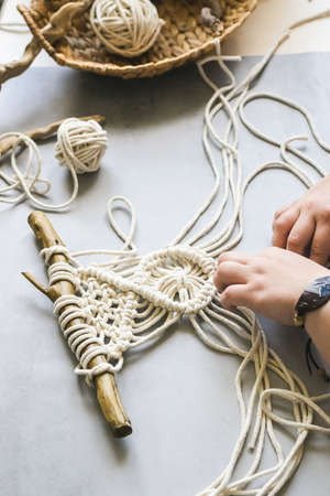 Female hands weave macrame the home workshop. Boho lifestyle. Hobby hobby concept. Selective focus Stockfoto